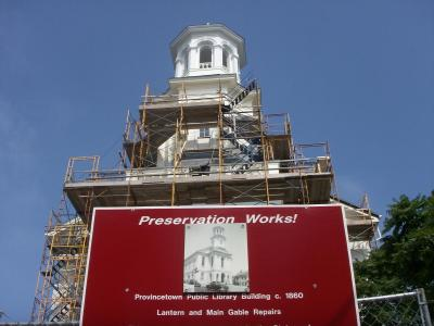 "Preservation of Provincetown's historic public library. The building is surrounded in scaffolding and work is underway. A red sign in front of the project site reads ""Preservation Works!"""
