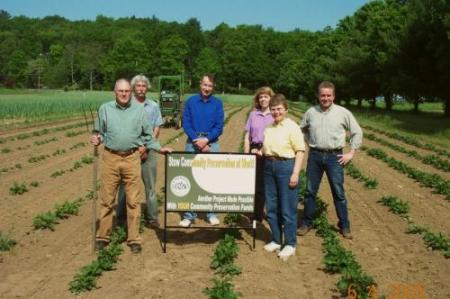 """Stow's Community Preservation Committee stands in a newly planted farm field around a sign that reads """"Stow Community Preservation at work, another project made possible with YOUR community preservation funds"""""""