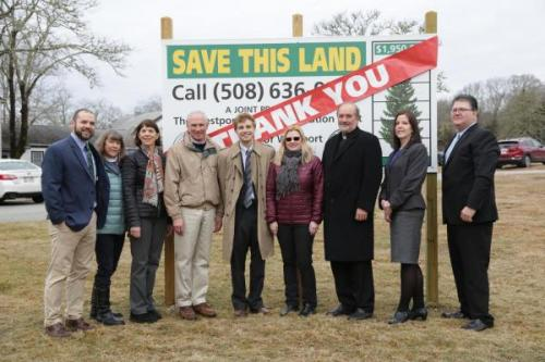 """A group of advocates in Westport stand in front of a sign charting progress in money raised to save the St. Vincent de Paul land. A large red banner reading """"thank you"""" is hung across the sign"""