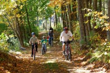 A family rides bikes on a trail through Plimpton Community Forest in Sturbridge