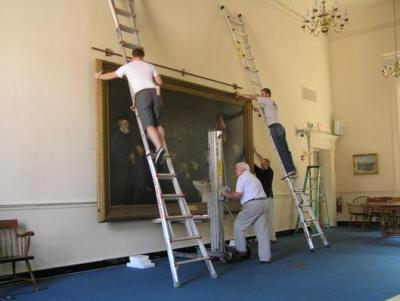 Historic Preservation in Concord. Four people work to rehang a historic work of art