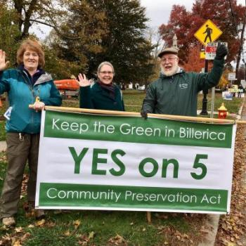 """CPA advocates and supporters in Billerica hold a large green and white banner reading """"Keep the Green in Billerica - YES on 5 - Community Preservation Act"""""""