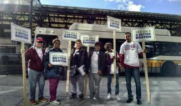 """A group of CPA advocates and supports in Boston stand together, all holding signs that read """"Yes on 5 For A Better Boston"""""""
