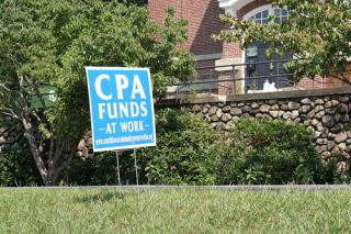 "A bright blue ""CPA funds at work"" sign on a grassy green lawn in Southborough"