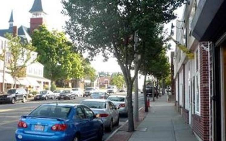 A sidewalk on a tree-lined Main Street. This type of project would not be allowable with CPA funds.